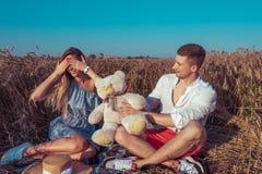 En ung parmankvinna, sommarvetefält, lyckligt le ger en gåva, leksakbjörn, vilar begrepp av förälskelse, datumet, sinnesrörelse royaltyfri foto
