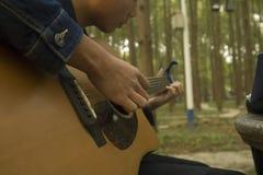 En ung pojke är den praktiserande gitarren arkivbild