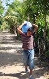 En ung pojke bär en stor flaska av vatten på hans baksida i lantligt Arkivfoton