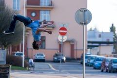 En ung pojke hoppar slår en kullerbytta på gatan Arkivbilder