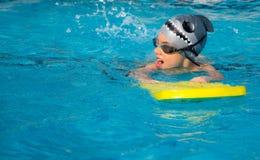 En ung pojke i simbassäng Arkivfoto