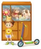 En ung pojke med hans sparkcykel och hans leksaker i ett kabinett Royaltyfri Foto