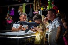 En ung pojke- och faderskytte med det automatiska vapnet för airsoft på en mässa arkivfoto
