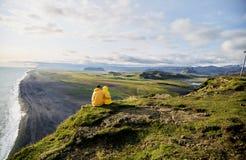 En ung pojke och flicka sitter på en klippa och en kram royaltyfri foto
