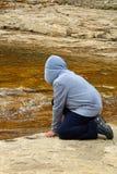 En ung pojke på flöda för vatten för flodkant hållande ögonen på arkivfoto