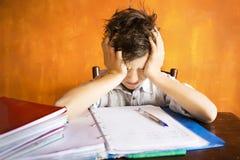 En ung pojke som är stressad på läxa Arkivfoton