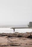 En ung pojke som kör ner en strand med havsskräp Arkivbilder