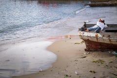 En ung pojke som lägger i ett fartyg som verkar att vara i djup tanke royaltyfri bild