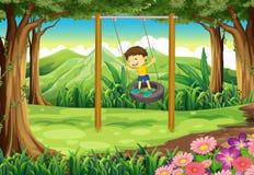 En ung pojke som spelar med gummihjulgungan Fotografering för Bildbyråer