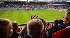 En ung pojke som tar en bild med en telefon i en fotbollsmatch Royaltyfria Foton