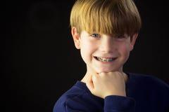 En ung pojke visar av hans gröna hänglsen Royaltyfria Foton