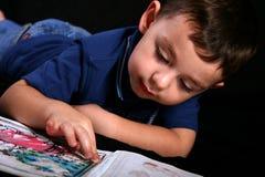 En ung pojkefingermålning en färgläggningbok Arkivbilder
