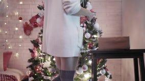 En ung prettty kvinna dekorerar en julgran med leksaker Närbildsikten räcker och lägger benen på ryggen lager videofilmer