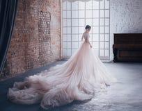 En ung prinsessa i en dyr lyxig klänning med ett långt drev står med henne tillbaka till kameran, mot royaltyfria foton