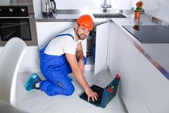 En ung repairman reparerar ett kökskåp med hjälpmedel arkivfoton