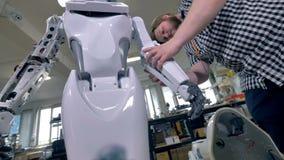 En ung repairman täcker robotstålramen på underarmen stock video