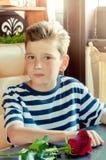 En ung romantisk pojke med en trendig frisyr och en ros Royaltyfri Foto