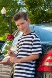 En ung romantisk pojke med en trendig frisyr och en ros Royaltyfri Bild