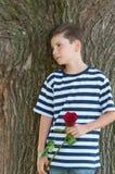 En ung romantisk pojke med en trendig frisyr och en ros Arkivbilder