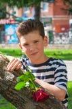 En ung romantisk pojke med en trendig frisyr och en ros Royaltyfria Bilder