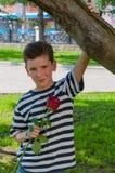 En ung romantisk pojke med en trendig frisyr och en ros Arkivfoto