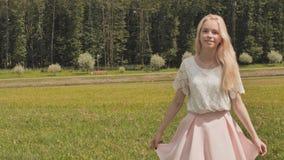 En ung rysk flickablondin som poserar i en stad, parkerar på en sommardag lager videofilmer