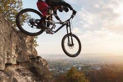 En ung ryttare på hjulet av hans mountainbike gör ett trick i banhoppning på språngbrädan av det sluttande berget royaltyfri fotografi