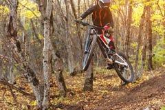 En ung ryttare på hjulet av hans mountainbike gör ett trick i banhoppning på språngbrädan av det sluttande berget arkivbilder