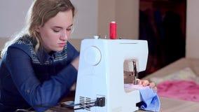 En ung sömmerska ställer in - upp en symaskin, börjar att sy kläder arkivfilmer