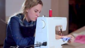 En ung sömmerska ställer in - upp en symaskin, börjar att sy kläder Fokus på symaskinen, ultrarapid lager videofilmer