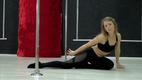 En ung sexig sexig danskvinna, en poly dansdans i korridoren runt om polen Arkivfoto