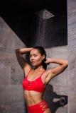 En ung sexig kvinna som bär den röda baddräkten som utanför duschar på det lyxiga hotellet Fotografering för Bildbyråer