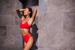 En ung sexig kvinna som bär den röda baddräkten som utanför duschar på det lyxiga hotellet Arkivfoto