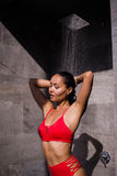 En ung sexig kvinna som bär den röda baddräkten som utanför duschar på det lyxiga hotellet Royaltyfri Foto