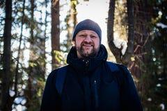 En ung skäggig man går till och med skogen och ler se dig fotografering för bildbyråer