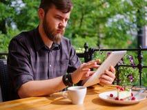 En ung skäggig man som använder hans bärbar dator, sitter i ett kafé Arkivfoto
