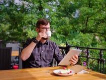 En ung skäggig man som använder hans bärbar dator, sitter i ett kafé Fotografering för Bildbyråer