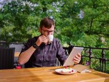 En ung skäggig man som använder hans bärbar dator, sitter i ett kafé Royaltyfria Bilder