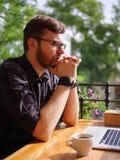 En ung skäggig man som använder hans bärbar dator, sitter i ett kafé Arkivfoton
