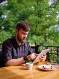 En ung skäggig man som använder hans bärbar dator, sitter i ett kafé Royaltyfria Foton