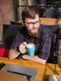 En ung skäggig man som använder hans bärbar dator, sitter i ett kafé Royaltyfri Bild