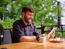 En ung skäggig man som använder hans bärbar dator, sitter i ett kafé Royaltyfri Foto