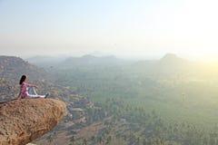 En ung skallig man sitter överst av ett berg mot en bakgrund Arkivbild