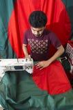 En ung skräddare Md Rashed Alam åldras 28 bangladeshiska nationsflaggor för danande på Dhaka, Bangladesh Arkivbild
