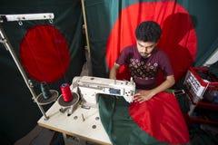 En ung skräddare Md Rashed Alam åldras 28 bangladeshiska nationsflaggor för danande på Dhaka, Bangladesh Arkivfoto