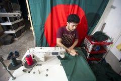 En ung skräddare Md Rashed Alam åldras 28 bangladeshiska nationsflaggor för danande på Dhaka, Bangladesh Royaltyfri Foto