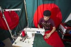 En ung skräddare Md Rashed Alam åldras 28 bangladeshiska nationsflaggor för danande på Dhaka, Bangladesh Royaltyfri Fotografi