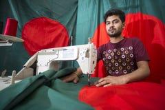 En ung skräddare Md Rashed Alam åldras 28 bangladeshiska nationsflaggor för danande på Dhaka, Bangladesh Royaltyfria Foton