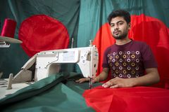 En ung skräddare Md Rashed Alam åldras 28 bangladeshiska nationsflaggor för danande på Dhaka, Bangladesh Fotografering för Bildbyråer