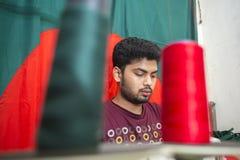 En ung skräddare Md Rashed Alam åldras 28 bangladeshiska nationsflaggor för danande på Dhaka, Bangladesh Royaltyfria Bilder